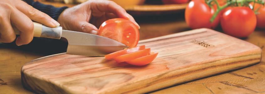 iemand snijdt een tomaat in schijfjes op een houten snijplank Qi-board