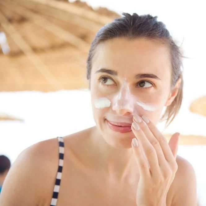 vrouw die gezicht insmeert met zonnebrandcrème