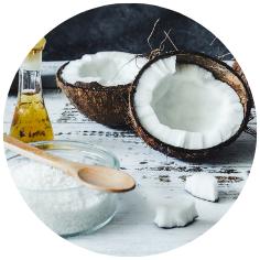 halve kokosnoten op witte houten tafel met potje kokosvlokken en kokosolie